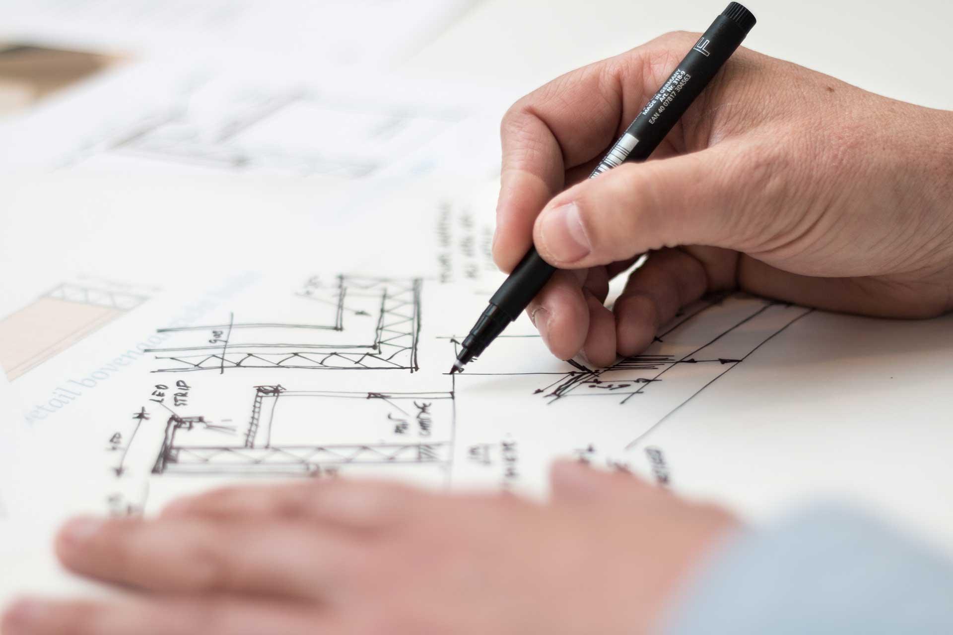 Hier sehen Sie einen Architekten, der einen Entwurf für eine Textilfassade gemeinsam mit der Planex Technik in Textil GmbH an einem Arbeitstisch erstellt.