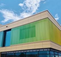 Hier sehen Sie ein Gebäude mit einer Textilfassade von Planex in Regenbogenfarben