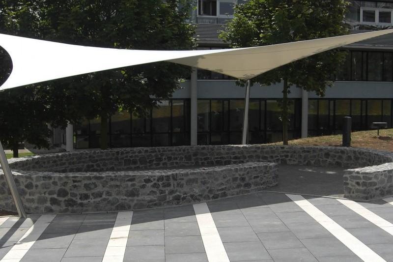 Ein Sonnensegel nach Maß an einem öffentlichen Platz vor einem Gebäude.